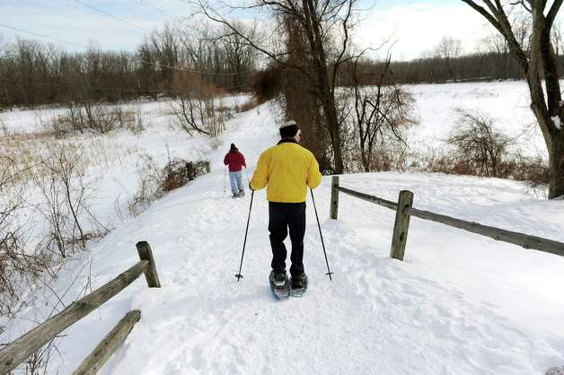 Carol Davis of Clifton Park, left, and her husband Bill Blain snowshoe on Wednesday, Feb. 18, 2015, at Vischer Ferry Nature and Historic Preserve in Clifton Park, N.Y. Clifton Park, with the Mohawk Towpath Byway, received $3,900 from Erie Canalway National Heritage Corridor to design and develop two trail entrance signs that identify the Vischer Ferry Nature & Historic Preserve?s entry points.(Cindy Schultz / Times Union) Photo: Cindy Schultz / 00030544A