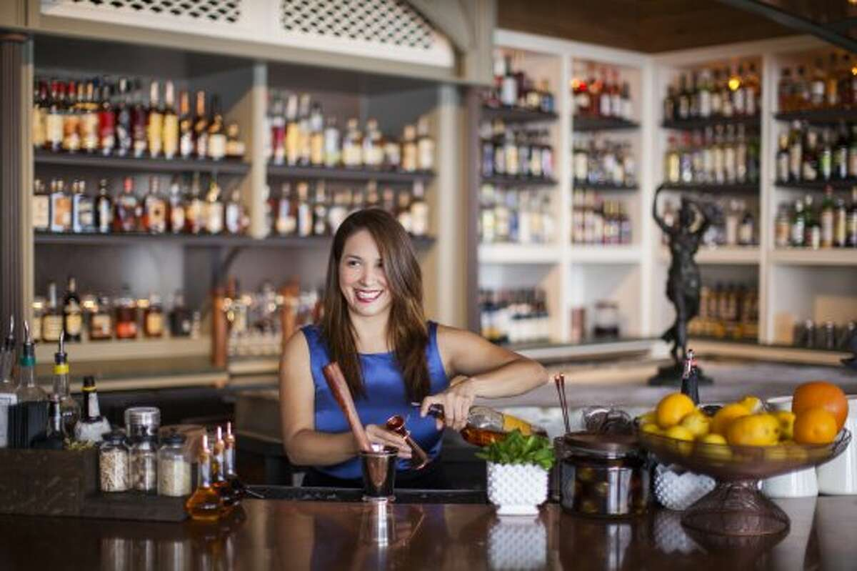 Alba Huerta mixing drinks at the bar she owns with Clumsy Butcher/Bobby Heugel.