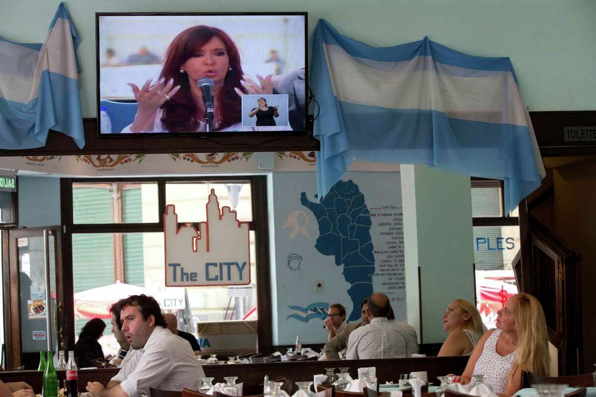 A TV shows a live image of Argentina's President Cristina Fernandez speaking at the Atucha nuclear power plant, as people eat inside a restaurant in Buenos Aires, Argentina, Wednesday, Feb. 18, 2015. The Argentine government's executive branch criticized the country's Justice Department on Wednesday, the latest verbal barb ahead of a protest being organized by investigating attorneys demanding answers in the mysterious death of prosecutor Alberto Nisman.