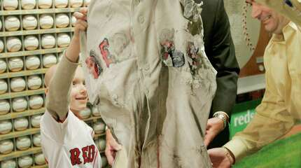 Ryan Reardon, of Groveland, Mass., left, an eight-year-old cancer patient at the Dana-Farber Cancer Institute, and Jerry House, of Reading, Mass., right, also a cancer patient at the hospital, unveil the jersey of Boston Red Sox baseball player  David Ortiz, that was buried under the New York Yankees new stadium, during ceremonies at the cancer institute in Boston Thursday April 17, 2008. The Red Sox's official charity, the Jimmy Fund, is auctioning off the jersey. The jersey was buried by a Boston fan trying to curse its American League rivals.
