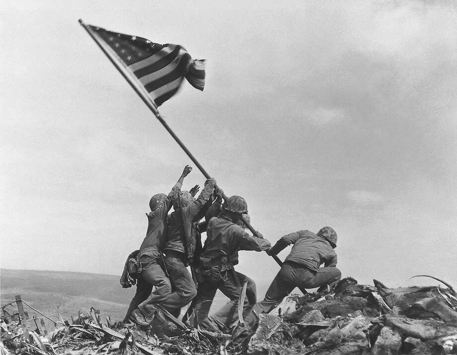 U.S. Marines of the 28th Regiment, 5th Division, raise the American flag atop Mt. Suribachi, Iwo Jima, on Feb. 23, 1945. Strategically located only 660 miles from Tokyo, the Pacific island became the site of one of the bloodiest, most famous battles of World War II against Japan. Photo: JOE ROSENTHAL, AP / 1945 AP
