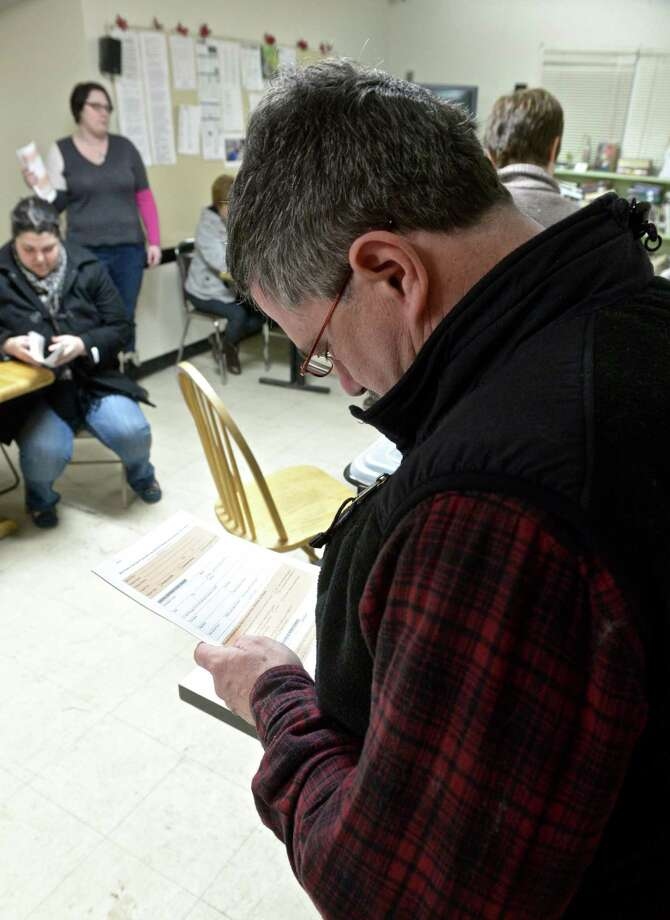 Bill Pierce, of Bristol, looks over one of the forms to be used during the annual Point in Time count of the homeless in the city, on Wednesday night, February 18, 2015, in Danbury, Conn. Pierce has been volunteering to help with the count for 5 or 6 years. Photo: H John Voorhees III / The News-Times