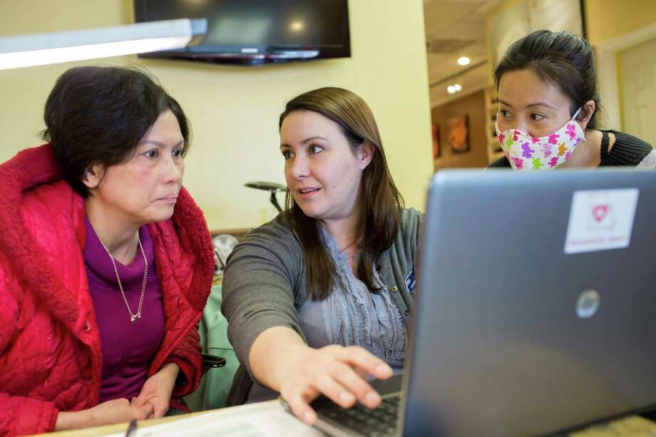 Vi Nguyen (right) translates for her sister-in-law, Kim Trinh (left), as Laura Burbank, a certified application counselor with Planned Parenthood, helped Trinh sign up for health insurance on HealthCare.gov. The Supreme Court will hear arguments Wednesday on whether the health law can provide subsidies nationwide to people who buy insurance or only to those in the states that have set up their own online marketplaces, known as exchanges. Photo: Whitney Curtis /New York Times / NYTNS