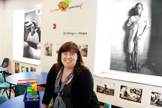 Heather Hickland, director of the World Awareness Children's Museum with a collection of photographs by Emma Dodge Hanson documenting the work of local nonprofit Drilling for Hope in its journey to bring clean, accessible water to villages around the world  on display at the museum Tuesday Feb. 17, 2015, in Glens Falls, NY.    (John Carl D'Annibale / Times Union) Photo: John Carl D'Annibale / 00030624A