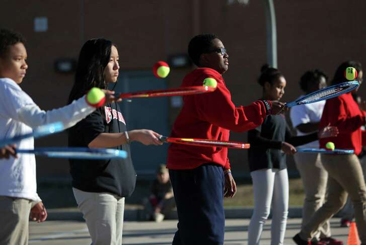 Crystal Dang, 13, eighth-grade, second from left, and Silas Miller, 13, third from left, seventh-grade, along with other middle school children participate in the Club Mid, teen after school enrichment program, learning the fundamentals of tennis at the Weekley Family YMCA Wednesday, Feb. 18, 2015, in Houston, Texas. ( Gary Coronado / Houston Chronicle )