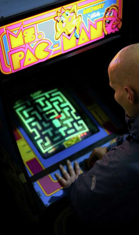 "Steve Philippeos, who enjoys spending his free time playing retro games, tries his luck at the classic game ""Centipede"" at Musee Mecanique. Photo: Amy Osborne / The Chronicle / ONLINE_YES"
