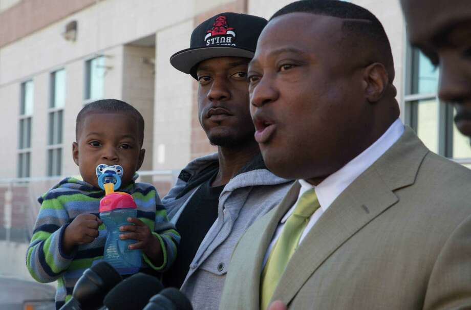 Fredrick Alsandor holds his son while activist Quanell X and Torrance Valentine address the media on Wednesday  at the Harris County Sheriff's Office in downtown. Cell phone footage and photographs taken by Valentine during a Feb. 11 traffic stop when he was pulled over by two deputies has been turned over to authorities. Photo: Billy Smith II, Chronicle / Houston Chronicle