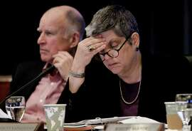 University of California President Janet Napolitano and Gov. Jerry Brown attend a regents meeting in San Francisco in 2013. On Wednesday, Napolitano announced she would delay tuition increases until after the summer session.
