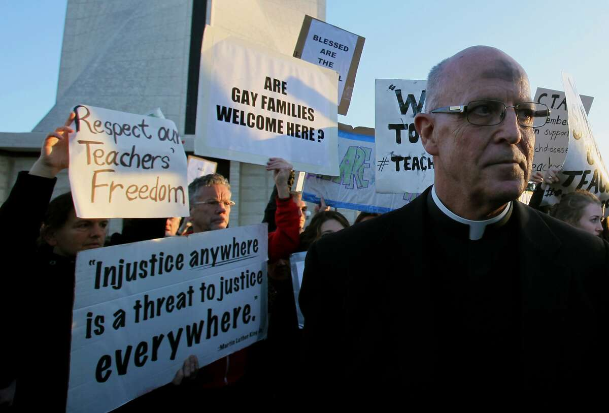 Father John Piderit from the Archdiocese of San Francisco protests with hundreds at Saint Mary's Cathedral against the archbishop's proposed