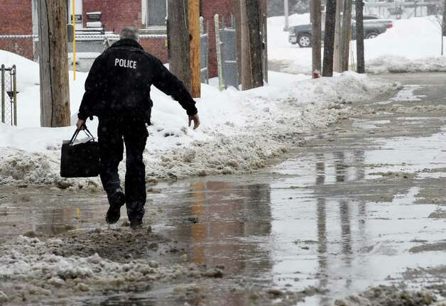 A Cohoes Police officer walks through a large amount of water on Canvas Street at the rear of City Hall after a water main break caused flooding Monday morning, Feb. 9, 2015, in Cohoes, N.Y.  (Skip Dickstein/Times Union) Photo: SKIP DICKSTEIN