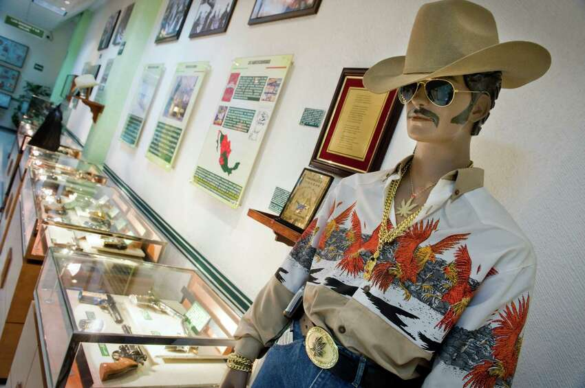 In Mexico City, the military has a museum used to train officials, diplomats, and cadets about the war on drugs. One room of the museum is dedicated to narco culture. It depicts one cartel member dressed in a garish shirt, cowboy hat and belt buckle. A row of glass cases are filled with seized weapons.