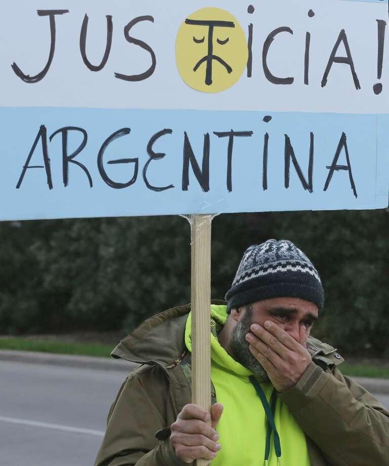 El argentino Germán Menzo se seca la lágrimas mientras marcha con otros compatriotas frente al consulado argentino el 18 de febrero de 2015. Photo: Thomas B. Shea, Para La Voz