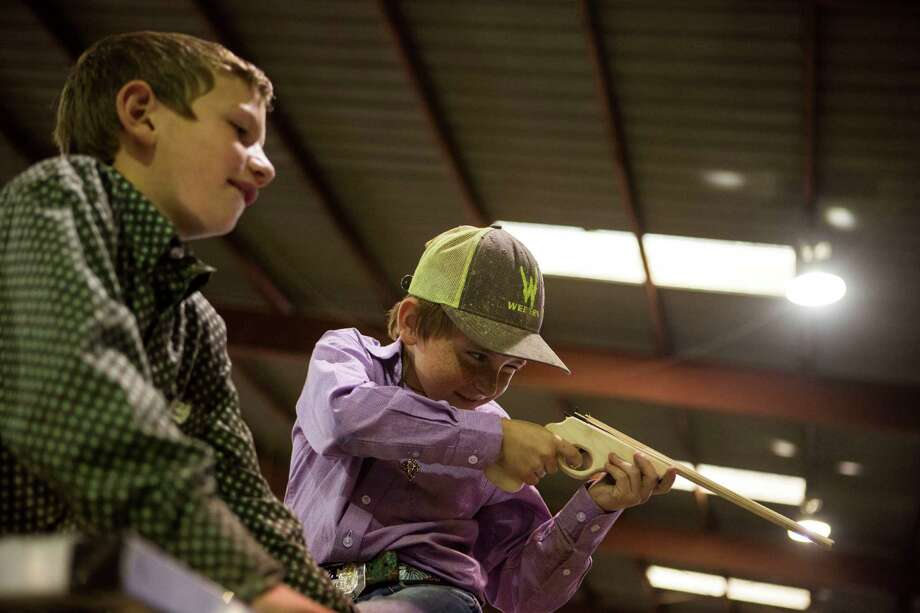 Trey Harbour, 9, watches his friend Costin Allison, 10, shoot rubber bands at Allison's father at the San Antonio Stock Show and Rodeo in San Antonio, TX on Wednesday, February 18, 2015. Photo: Carolyn Van Houten, San Antonio Express-News / 2015 San Antonio Express-News