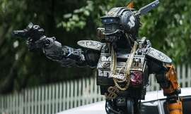 "Chappie (Sharlto Copley) shoots guns, so he's one of the bad AI robots, right? We're just guessing. A still from ""Chappie."""