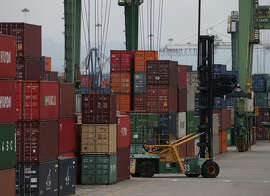 A forklift moves through containers at the Port of Oakland as work resumed in February.
