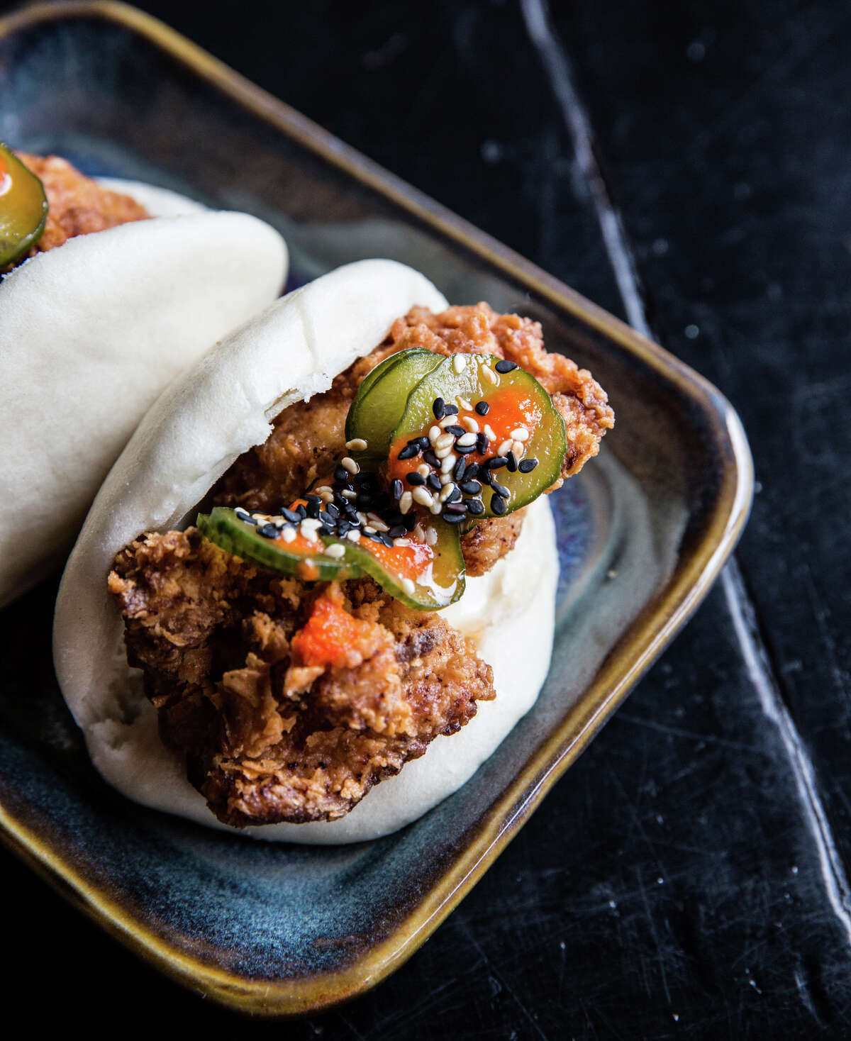 A study in contrasts: Hapa Ramen's buttermilk fried chicken steamed bun features a satisfying juxtaposition of crisp fried chicken and soft bun that's complemented by tangy hot sauce and creamy mayo.