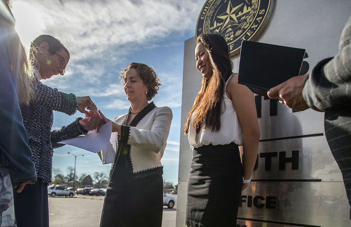 Suzanne Bryant places the ring on Sarah Goodfriend ring finger as their daughters Ting , far left and Dawn look on, during the marriage ceremony with Rabbi Kerry Baker outside of the Travis County Clerk's office in Austin, Texas on Thursday, Feb. 19, 2015. The marriage followed a state District Court order instructing that officials not rely on Texas' unconstitutional prohibitions on same-sex marriage. Texas' decade-old, voter-approved ban on gay marriage was declared unconstitutional in federal court last year, but the judge stayed the ruling to allow the state to appeal. (AP Photo/Austin American-Statesman, Ricardo B. Brazziell) AUSTIN CHRONICLE OUT, COMMUNITY IMPACT OUT, INTERNET AND TV MUST CREDIT PHOTOGRAPHER AND STATESMAN.COM, MAGS OUT