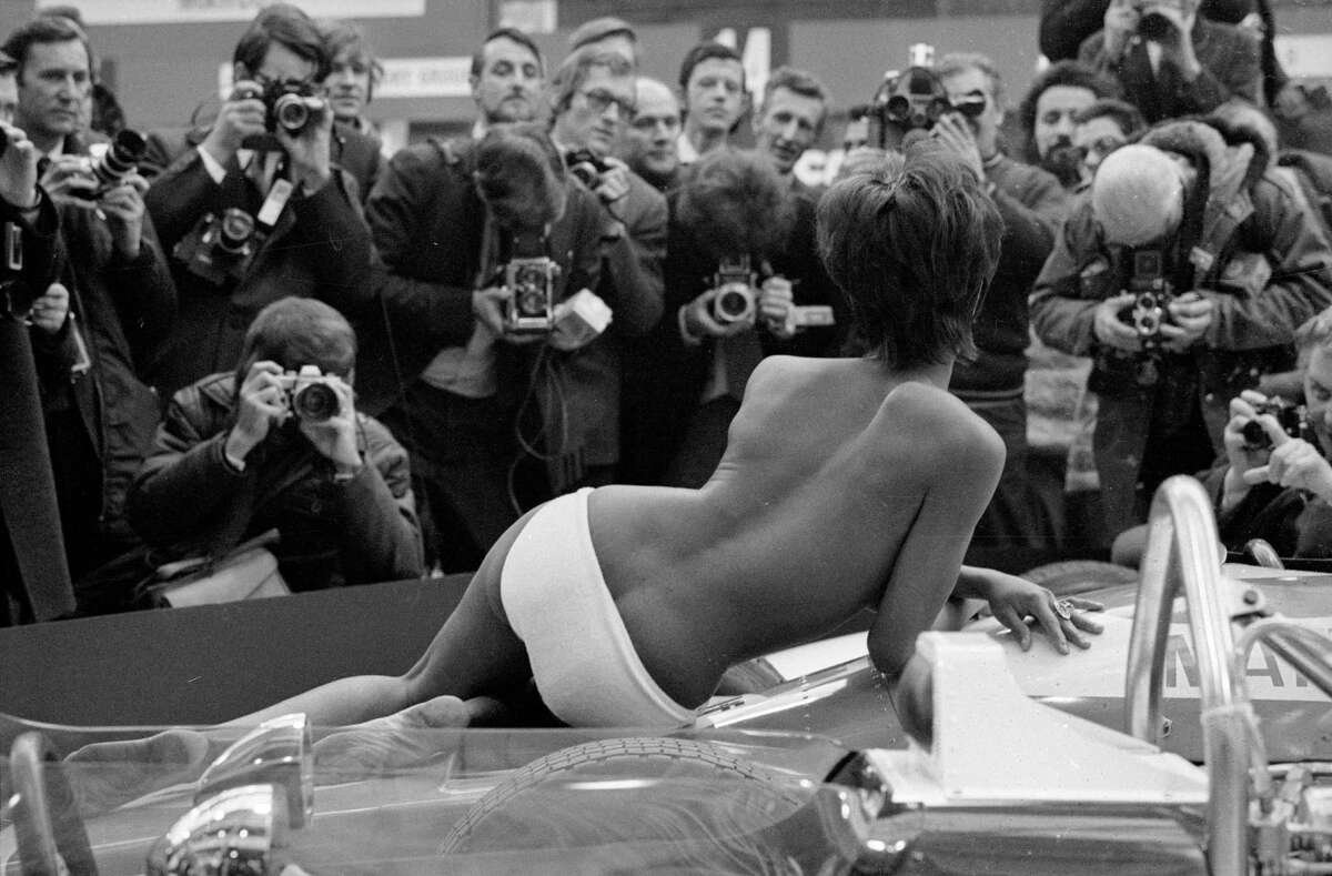 But one thing remains the same: Sex sells. Here photographers crowd around a topless model posing on one of the exhibits at the 1971 Racing Car Show at Olympia, London.
