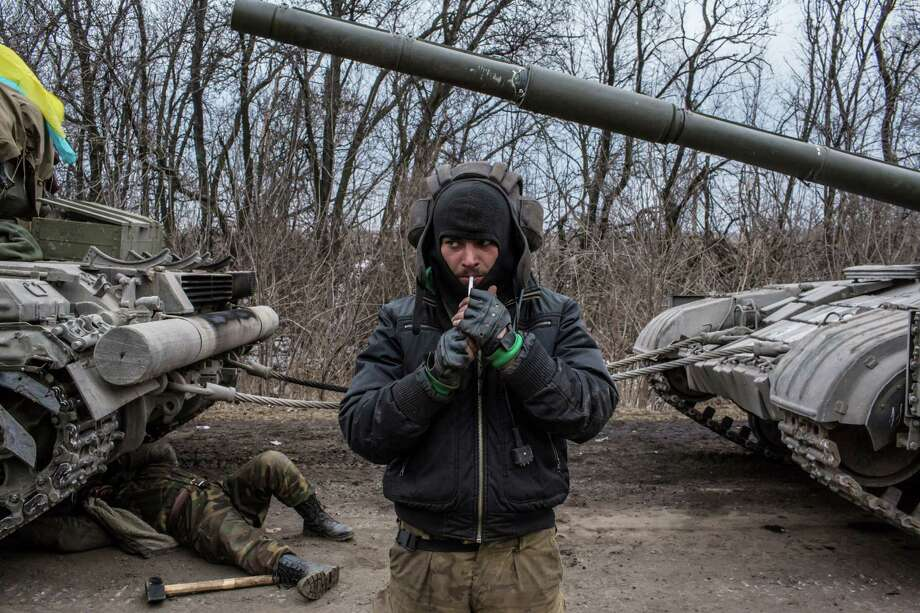 A Ukrainian soldier lights a cigarette while his unit's tank is repaired on a roadside leading out of Debaltseve in Artemivsk, Ukraine. Ukrainian forces have begun withdrawing from the strategic and hard-fought town of Debaltseve after being effectively surrounded by pro-Russian rebels. Photo: Brendan Hoffman / Getty Images / 2015 Getty Images