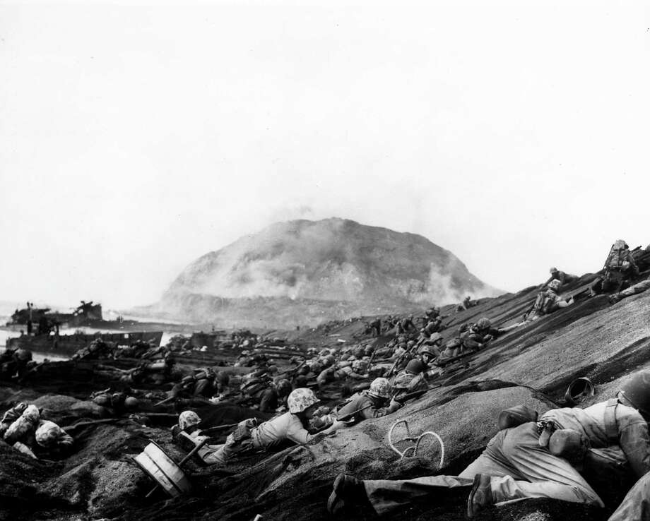 American Marines advancing up beaches after landing on Iwo Jima to oust the occupying Japanese troops and secure an air base close to Japan. Photo: Louis R. Lowery, Getty / Time Life Pictures