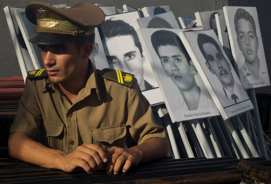 In this Sept. 20, 2014 photo, a military academy student rests next to a photos of people who died in the 1976 Cubana Airlines bombing as it was flying from Barbados to Cuba, in Havana, Cuba. Many Cubans describe the bombing that killed 73 people as the worst act of aggression against the island since its 1959 revolution. The bombing is blamed on exiles with ties to U.S.-backed anti-Castro groups, and both of the men accused of masterminding the crime took shelter in Florida, where one, Luis Posada Carriles, lives quietly to this day. (AP Photo/Ramon Espinosa) Photo: Ramon Espinosa / Associated Press / AP