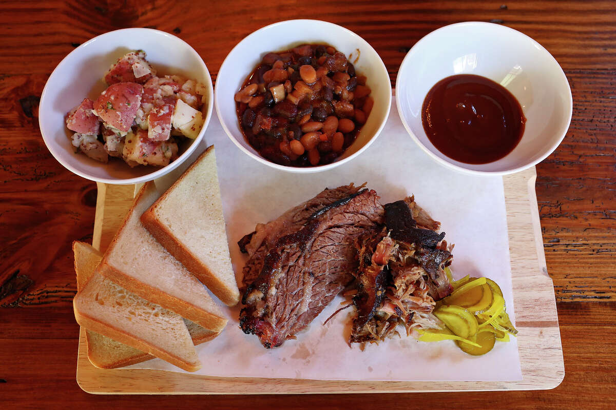 Barbecue board with baked beans, potato salad, buttermilk bread, pickles and 'cue sauce
