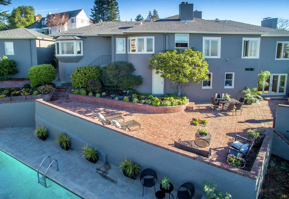 The terraced backyard hosts a brick patio and pool with concrete surround. Photo: Tony Mills/Spark Solutions / ONLINE_CHECK