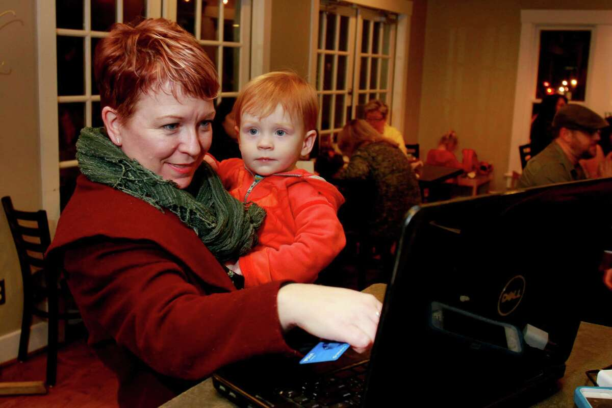 Katy Heinlein, holding her two-year-old son, Eli, makes a donation to Sean Carroll's kickstarter campaign. Sean and his wife, Tish Ochoa, kicked off the campaign with a party at Good Dog Hot Dog on Studewood. Sean is the chef/owner of the wildly popular mobile kitchen known as Melange Creperie. Sean's initial goal to raise $50,000. But he says if the campaign can raise $100,000, then he would be able to reach his ultimate goal, keeping his business in Montrose. (For the Chronicle/Gary Fountain, February 4, 2015)