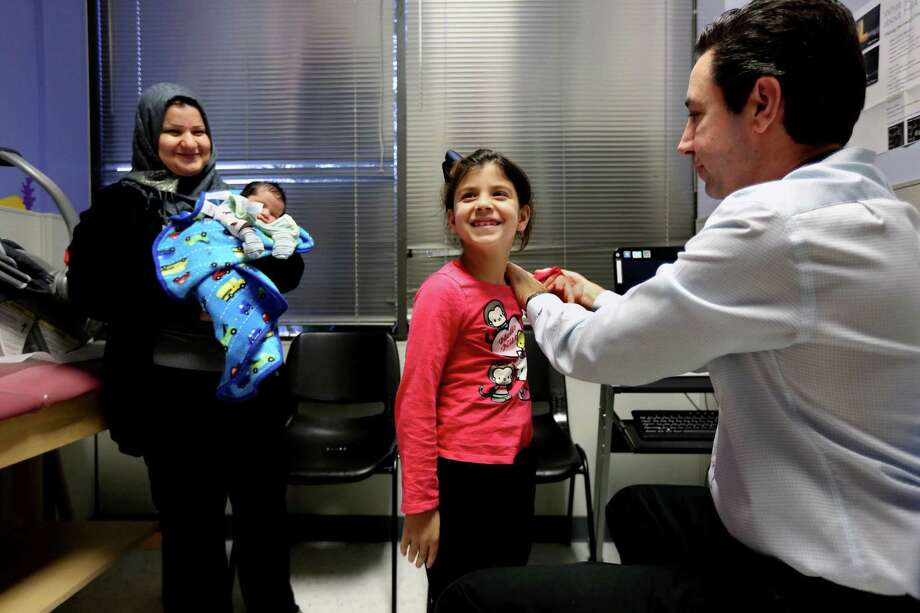 Dr. Peter Palmieri examines Fatimah Hussein, 7, while her mother, Hiba Kadham, holds newborn brother Mosa Hussein at HOPE Clinic, a community health center established by the Asian American Health Coalition. Photo: Gary Coronado, Staff / © 2015 Houston Chronicle