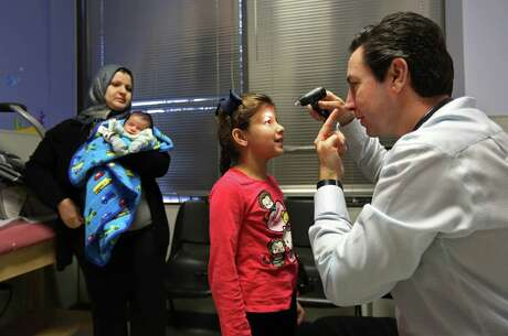 Dr. Peter Palmieri, of the pediatrics group, examines Fatimah Hussein, seven, while her mother Hiba Kadham and newborn brother Mosa Hussein, 20-days, looks on, at HOPE Clinic, a community health center established by the Asian American Health Coalition, Tuesday, Feb. 10, 2015, in Houston, Texas. ( Gary Coronado / Houston Chronicle )