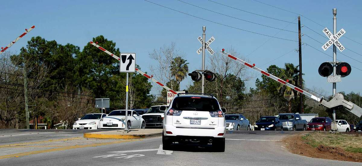 Crossing arms rise after a train passes and drivers had to wait to cross over the railroad tracks at the intersection of FM 359 and U.S. 90A on Feb. 9 near Richmond.