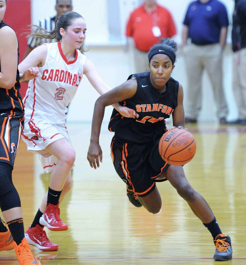 At right, Tiana England (#24) of Stamford beats Caroline Beneville (#2) of Greenwich, left, during the high school basketball game between Greenwich High School and Stamford High School at Greenwich, Conn., Wednesday, Dec. 10, 2014. Photo: Bob Luckey / Greenwich Time