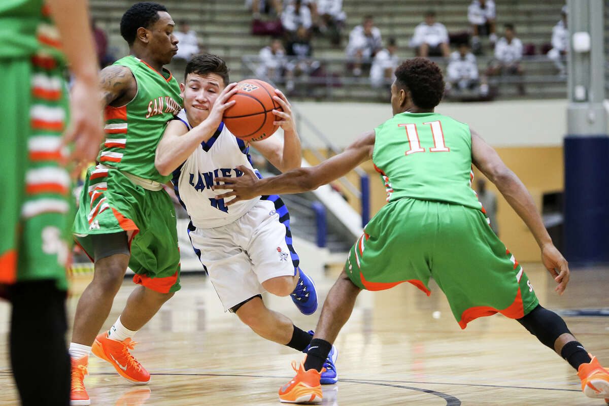 Lanier's Joe Soto (center) drives between Sam Houston's Juwan Anderson (right) and Dewayne Brown during the second half of their game at the Alamo Convocation Center on Friday, Feb. 13, 2015. Sam Houston beat the Voks 72-60.