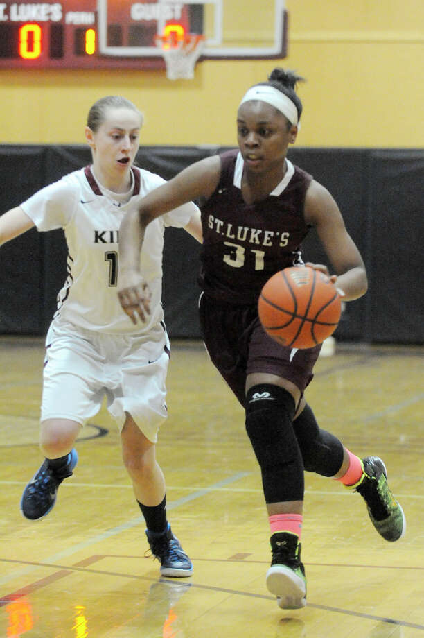 St. Luke's School's Sydney Lowery drives towards the basket past King's Natalie Wind during their basketball game at St. Luke's School in New Canaan, Conn., on Thursday, Feb. 19, 2015. St. Luke's won, 53-47. Photo: Jason Rearick / Stamford Advocate