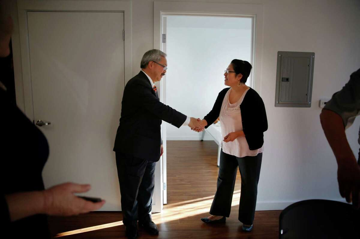 Mayor Ed Lee (l to r) and Sandra Melchor shake hands after he handed the keys to her new apartment at 1180 Fourth Street on Thursday, October 2, 2014 in San Francisco, Calif.