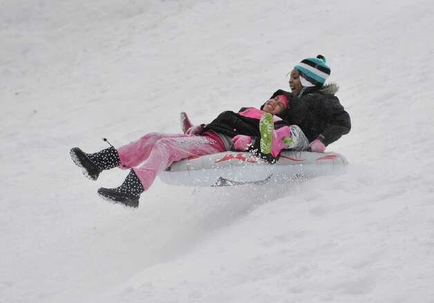 Gianna Grevely, left, 8, and her cousin Athena Hooper, 6, hit a jump on their sled at Central Park on Thursday, Feb. 19, 2015, in Schenectady, N.Y.    (Paul Buckowski / Times Union) Photo: STAFF / 00030689A