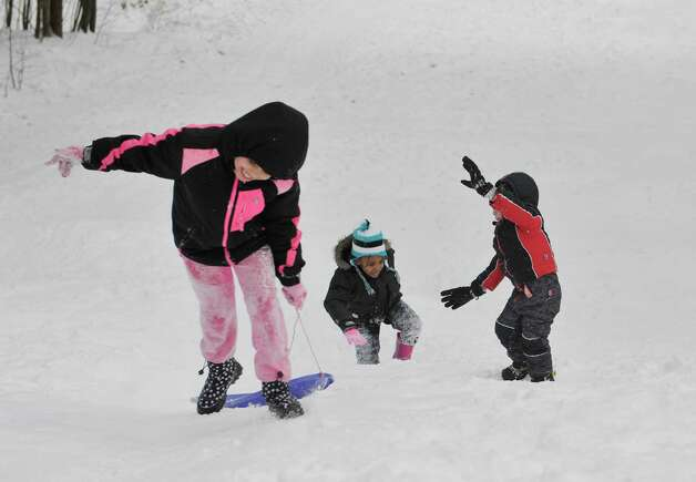 Gianna Grevely, left, 8, her cousin Athena Hooper, center, 6, and their friend Connor Conklin, 4, struggle up the hill for another sled ride down at Central Park on Thursday, Feb. 19, 2015, in Schenectady, N.Y.    (Paul Buckowski / Times Union) Photo: STAFF / 00030689A