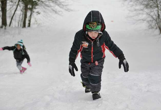 Connor Conklin, foreground, 4, and Athena Hooper, 6, make their way back  up the hill for another sled ride down at Central Park on Thursday, Feb. 19, 2015, in Schenectady, N.Y.    (Paul Buckowski / Times Union) Photo: STAFF / 00030689A