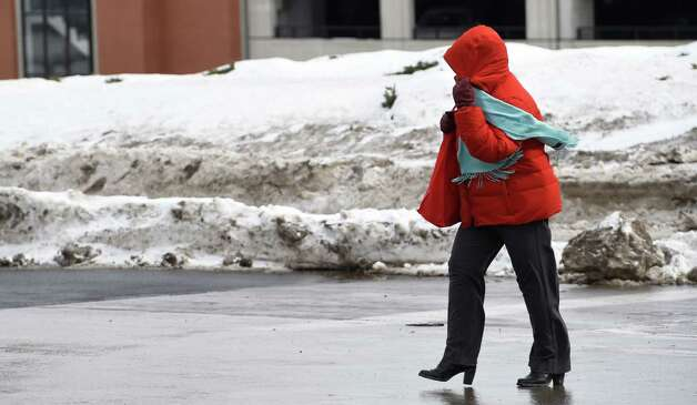 A pedestrian holds her hood closed on her jacket to protect herself from the wind near the Empire State Plaza Thursday afternoon, Feb. 19, 2015, in Albany, N.Y.   (Skip Dickstein/Times Union) Photo: SKIP DICKSTEIN