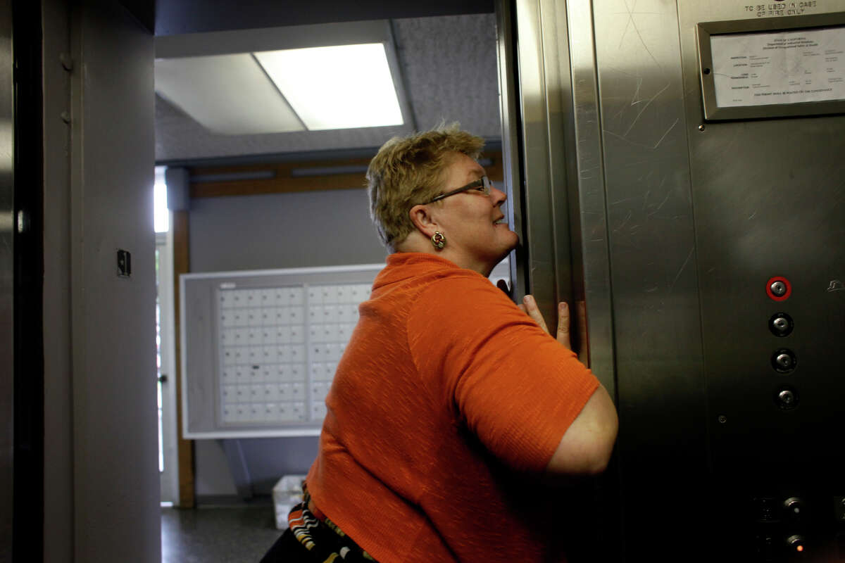 Richmond Housing Authority official Debra Holter pushes and squeezes the elevator doors to get it to work in the Hacienda public housing complex in February 2014.