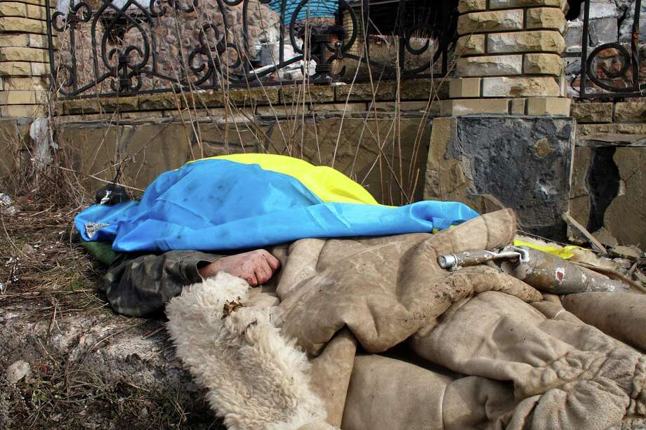 A body of a government soldier lies by the side of the road and is covered by a Ukrainian national flag in the east Ukraine town of Debaltseve on Thursday, Feb. 19, 2015. After weeks of relentless fighting, the embattled Ukrainian rail hub of Debaltseve fell Wednesday to Russia-backed separatists, who hoisted a flag in triumph over the town. The Ukrainian president confirmed that he had ordered troops to pull out and the rebels reported taking hundreds of soldiers captive. (AP Photo/ Peter Leonard) Photo: Peter Leonard, STF / AP