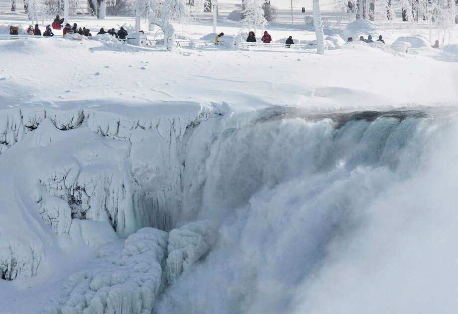 Niagara Falls State Park visitors look over masses of ice formed around the American Falls, photographed from across the Niagara River in Niagara Falls, Ontario, Canada, Thursday, Feb. 19, 2015. Photo: Aaron Lynett, Associated Press / The Canadian Press