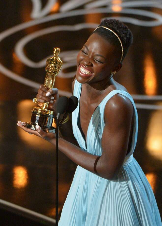 """FILE - In this March 2, 2014 file photo, Lupita Nyong'o accepts the award for best actress in a supporting role for """"12 Years a Slave"""" during the Oscars in Los Angeles. Nyong'o dazzled Hollywood and the Oscar-viewing public through awards season last year. The Mexican-born, Kenyan-raised actress was a central part last year to an Academy Awards flush with faces uncommon to the Oscar podium. There was Ellen DeGeneres, a proud lesbian, hosting. There was the first Latino, Alfonso Cuaron, winning best director. There was the black filmmaker Steve McQueen hopping for joy after his """"12 Years a Slave"""" won best picture. (Photo by John Shearer/Invision/AP, File) Photo: John Shearer, Associated Press"""
