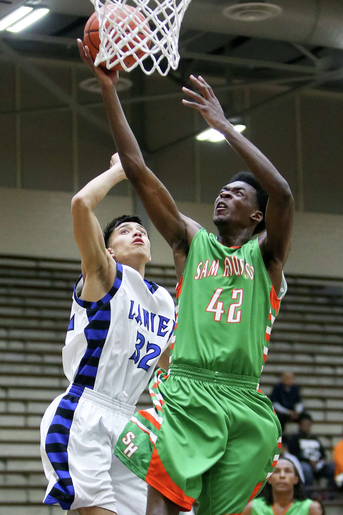 Sam Houston's Devin Allen (42) goes to the basket past Lanier's Luis Martinez (32) during the first half of their game at the Alamo Convocation Center on Friday, Feb. 13, 2015. Allen led all scorers with 20 points to help Sam Houston beat Lanier 72-60, handing the Voks their first district 28-5A loss. MARVIN PFEIFFER/ mpfeiffer@express-news.net