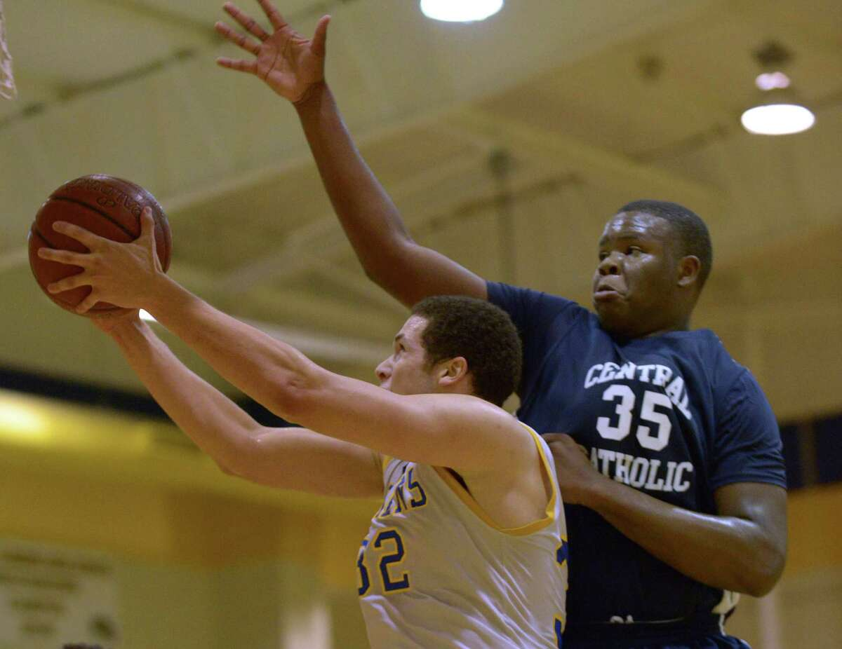 Cayne Edwards, (32) of Clemens shoots a layup as Tony Lewis of Central Catholic (35) defends during boys basketball action in Schertz on Saturday, Nov. 29, 2014.