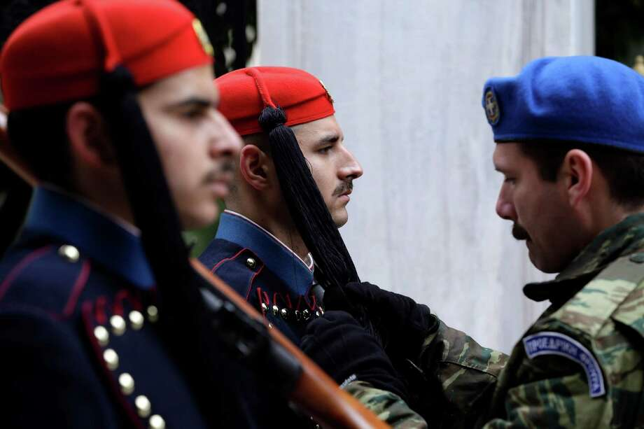 A military officer adjusts the uniforms of Greek presidential guards in Athens this week.   Photo: Thanassis Stavrakis, STF / AP