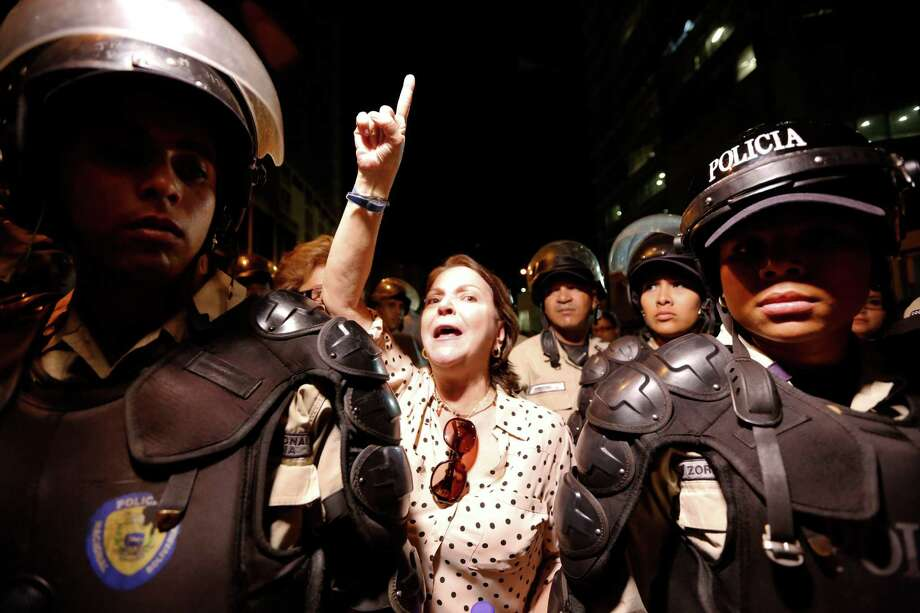 Mitzy Capriles de Ledezma, the wife of Caracas Mayor Antonio Ledezma, chants for the release of her husband, as she stands behind two national police officer on guard outside intelligence service police headquarters, in Caracas, Venezuela, Thursday, Feb. 19, 2015. Men in camouflage uniforms smashed into Ledezma's office on Thursday and carried the opposition figure away. An aide said some of the officers wore the uniform of the national intelligence service police. (AP Photo/Ariana Cubillos) Photo: Ariana Cubillos, STF / AP