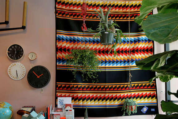 A colorful Pendleton blanket, houseplants and clocks near the front entrance of Aggregate Supply, which has everything from original designer clothes made locally to houseplants.