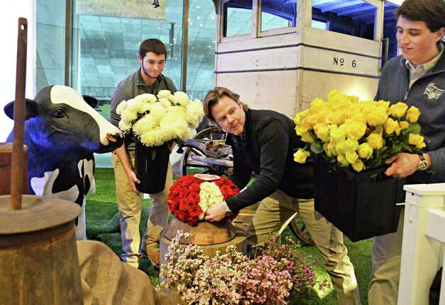 """David Michael Schmidt, center, and his team from Renaissance Floral Design on Western Avenue, Christopher Gallione, left, and Cody Swift set up their """"Old McDonald had a Farm"""" display Thursday Feb. 19, 2015, in the lobby of the NYS Museum for the annual New York in Bloom show in Albany, NY.  (John Carl D'Annibale / Times Union) Photo: John Carl D'Annibale / 00030443A"""