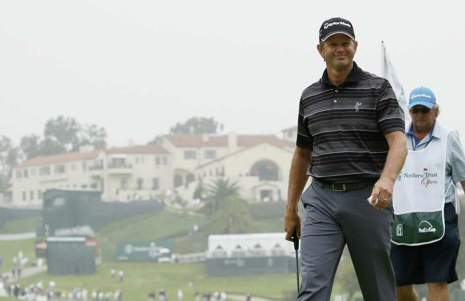 Retief Goosen of South Africa is all smiles after making birdie on No. 10 en route to shooting a 5-under 66 and tying for the lead at the Northern Trust Open. Photo: Danny Moloshok, FRE / FR161655 AP